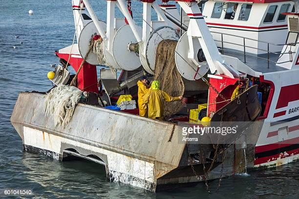 Fishermen working on board of fishing trawler / dragger at sea