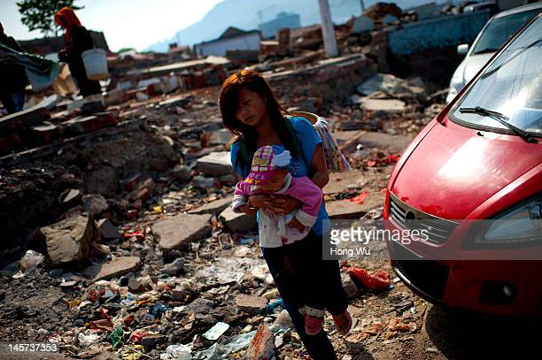A fisherwoman coming from Ziyang of Sichuan province holds her baby passing by a demolished fishing village at a port on May 23 2012 in Qingdao China...