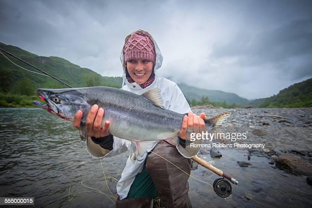 Fisherwoman holding up caught pink salmon in river, Kodiak, Alaska, USA