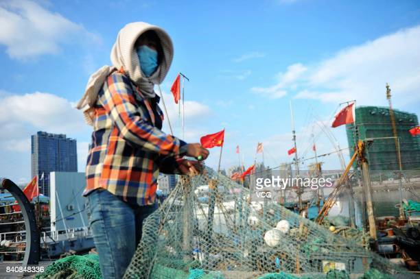 A fisherwoman mends fishing nets at a fishing port on August 30 2017 in Qingdao Shandong Province of China Fishing ban started from May 1 on China's...