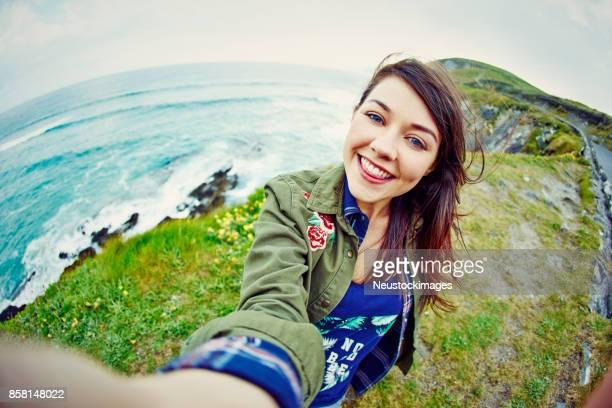 Fish-eye lens of happy woman taking selfie on mountain