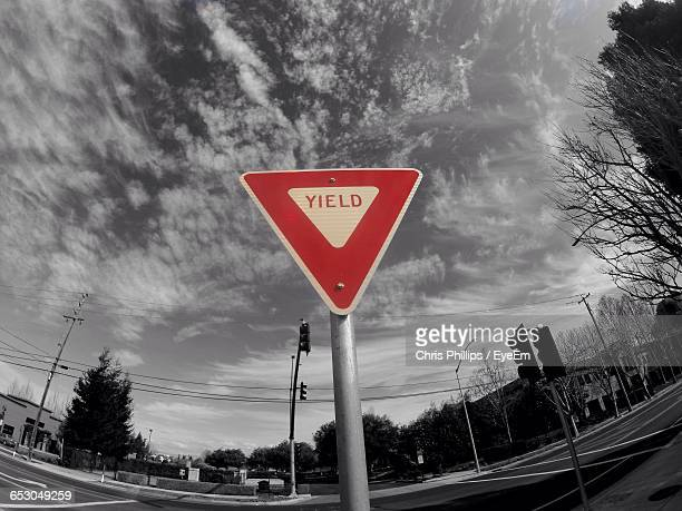 Fish-Eye Lens Of Yield Sign Against Sky