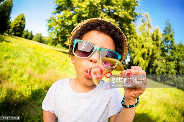 Retrato de olho-de-peixe rapaz Soprar de bolhas durante o Verão