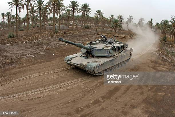 Fisheye style image of a tank driving on a dirt road