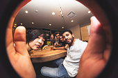 Group of colleagues celebrating their recent success of a business deal, after work, taking a fish-eye selfie