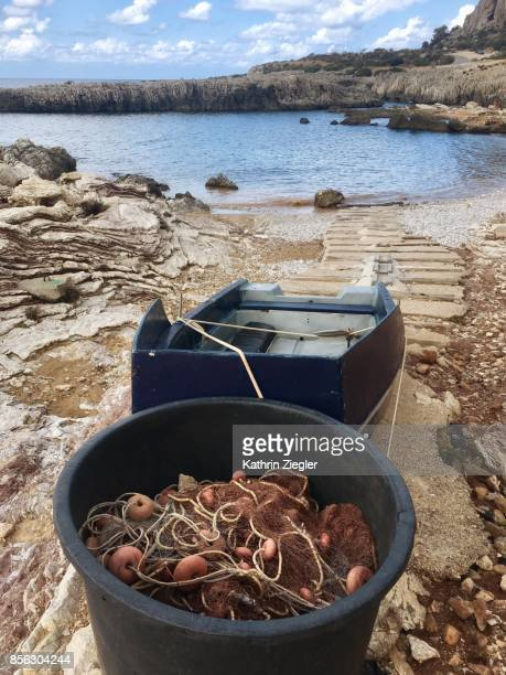 Fishing boat and net in small bay, Sicily