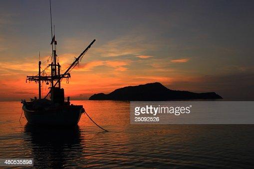 Fishing boat and sunrise : Stock Photo