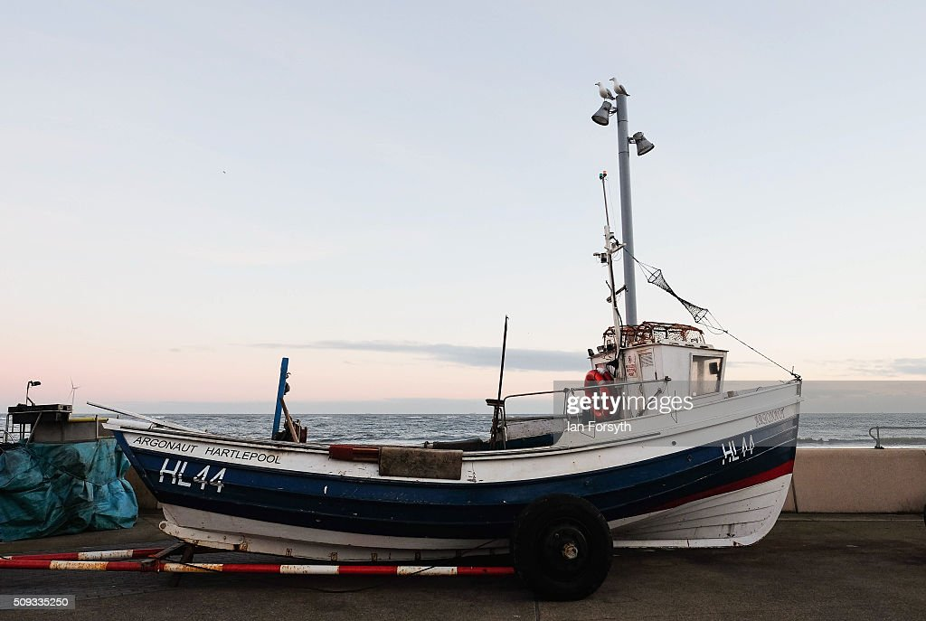 A fishing boat and trailer are parked on the seafront on February 10, 2016 in Redcar, England. The inshore fishing fleet at Redcar originated in the early 14th Century with crab, lobster and fishing bringing in much needed income to local fishermen. As the fishing industry has steadily declined so to the fleet has reduced in size so that today only a small number of boats still put to sea from the town to continue the fishing heritage on the east coast of England.