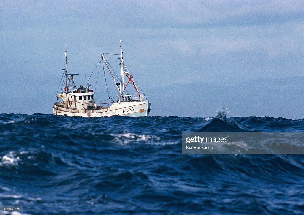 Fishing boat at sea stock photo getty images for Sea fishing boats