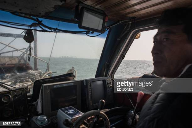 A fishing boat captain steers his vessel towards the salvage operation of the Sewol ferry off the coast of the southern South Korean island of Jindo...
