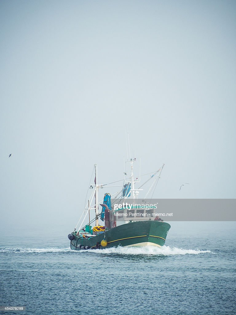 A fishing boat coming in from the mist
