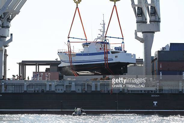 A fishing boat constructed by the Mechanical Constructions of Normandy is loaded on a cargo ship on July 10 2014 in Cherbourg en route to Mozambique...