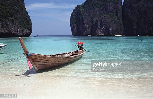 A fishing boat drawn up on the white sparkling beaches of Maya Bay Ko Phi Phi in Southern Thailand Turquoise seas and sandy beaches have made the Ko...