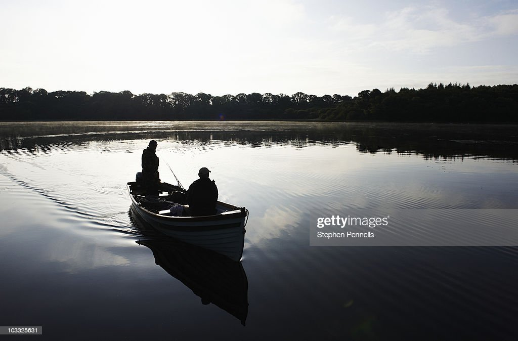 Fishing boat in silhouette on lake at dawn stock photo for Lake fishing boats