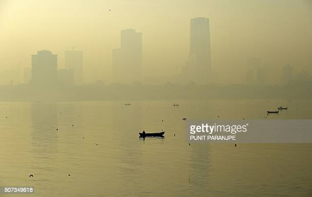 TOPSHOT A fishing boat is seen in the morning general view of the city skyline covered by a smoggy haze in Mumbai on January 29 2016 AFP PHOTO /...