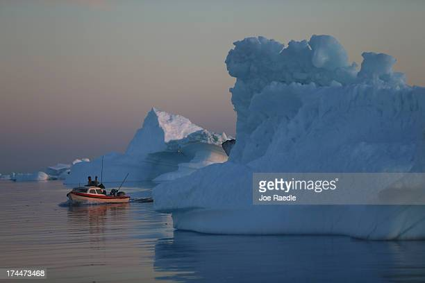 A fishing boat navigates past icebergs that broke off from the Jakobshavn Glacier on July 23 2013 in Ilulissat Greenland As the sea levels around the...