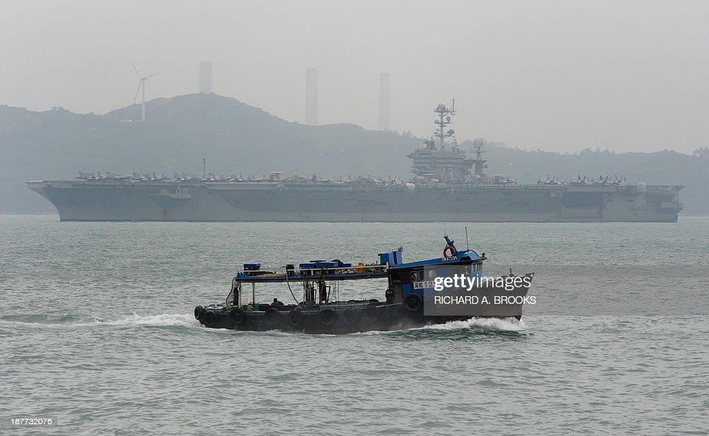 A fishing boat (foreground) passes by the aircraft carrier USS George Washington (background) as it sails out of Hong Kong on November 12, 2013 to join the rescue and relief operations in the Philippines following Super Typhoon Haiyan. US and British warships were deployed on November 12 to the typhoon-ravaged Philippines where well over 10,000 people are feared dead and countless survivors are begging for help in rain-soaked wastelands. Four days after Super Typhoon Haiyan destroyed entire coastal towns in mostly poor central islands with record winds and tsunami-like waves, the magnitude of the disaster continued to build with almost unimaginable horror. AFP PHOTO / RICHARD A. BROOKS