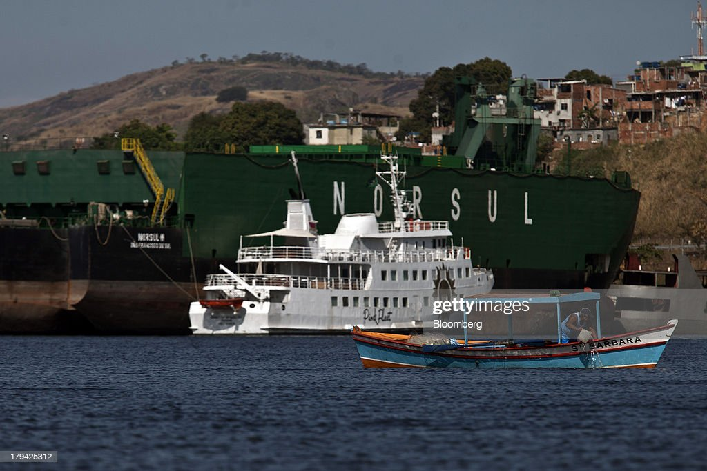 A fishing boat passes in front of Brazilian businessman Eike Batista's yacht, registered as Spirit of Brazil VII and known as the Pink Fleet, anchored in the Cassinu shipyard in Sao Goncalo, Brazil, on Thursday, Aug. 29 , 2013. The Pink Fleet party boat has left Rio de Janeiros main marina, possibly for the scrap heap, as former billionaire Eike Batista unloads luxury assets and retracts from public view after his highly-publicized downfall. Photographer: Dado Galdieri/Bloomberg via Getty Images