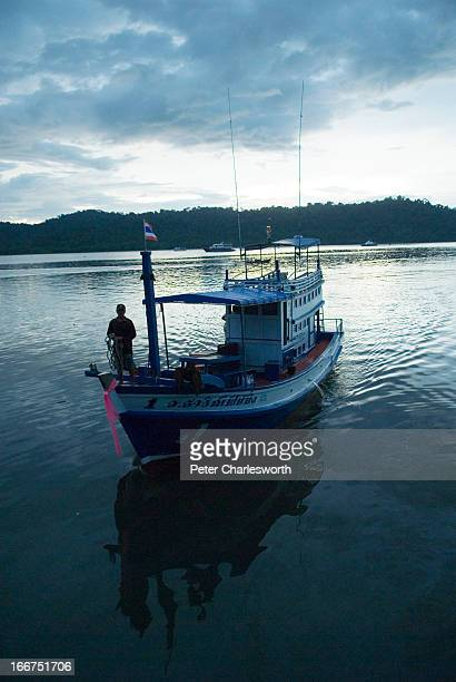A fishing boat pulls into the harbour at Tablamu in Phangnga at dusk