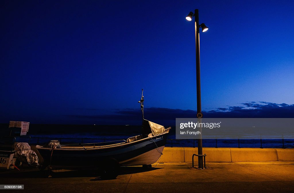 A fishing boat resting on a trailer used by tractors to tow it to the sea is lit by a streetlight above as it is parked on the seafront on February 10, 2016 in Redcar, England. The inshore fishing fleet at Redcar originated in the early 14th Century with crab, lobster and fishing bringing in much needed income to local fishermen. As the fishing industry has steadily declined so to the fleet has reduced in size so that today only a small number of boats still put to sea from the town to continue the fishing heritage on the east coast of England.