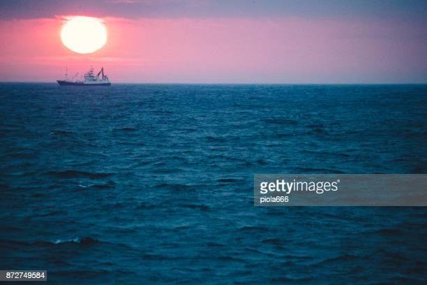 Fishing boat sailing rough sea at dawn