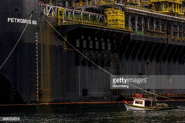 A fishing boat sails past a Petroleo Brasileiro SA Floating Production Storage and Offloading vessel at a maintenance shipyard in Angra dos Reis...