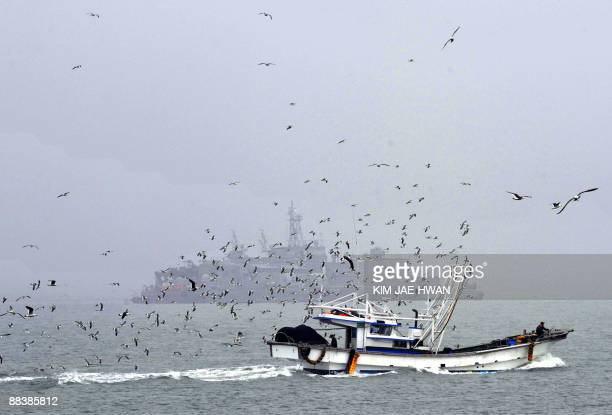 A fishing boat sails past a South Korean navy MSB off the South Koreacontrolled Yeonpyeong island on June 10 near the waters of the Yellow Sea...