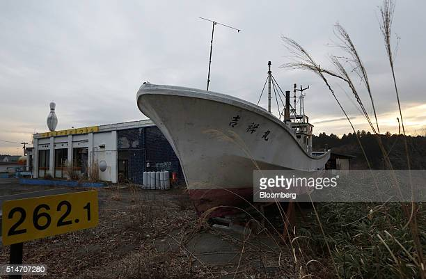 A fishing boat swept inland by a tsunami following the 2011 earthquake sits next to a bowling alley in an evacuation zone in Namie Fukushima...