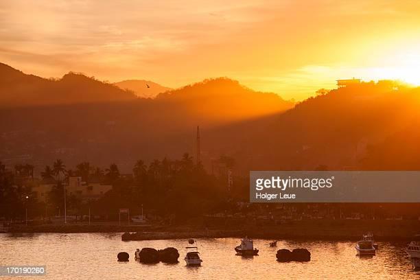 Fishing boats and hills at sunrise