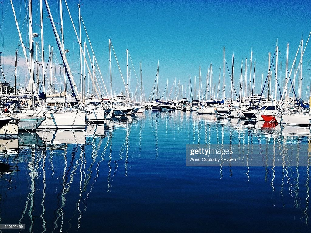 Fishing boats at harbor against blue sky