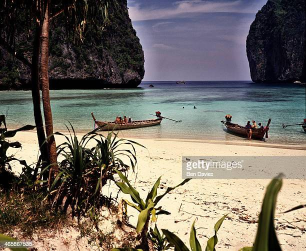 Fishing boats drawn up on the white sparkling beaches of Maya Bay Ko Phi Phi in Southern Thailand Turquoise seas and sandy beaches have made the Koh...