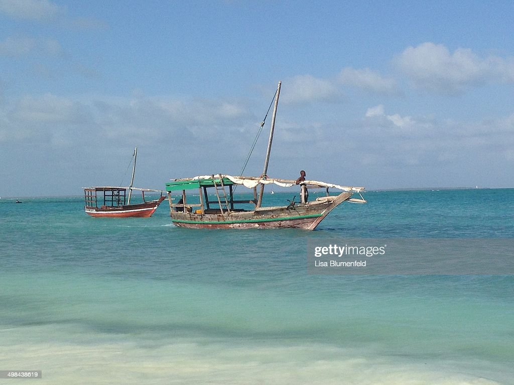 Fishing boats float on the Indian Ocean just off the ahore of Zanzibar, Tanzania, Africa.
