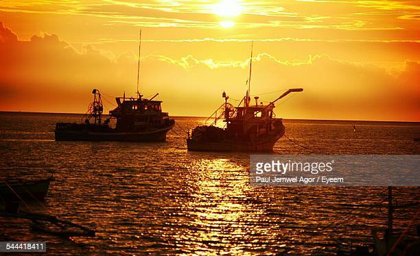 Fishing Boats In Sea Against Cloudy Sky During Sunset