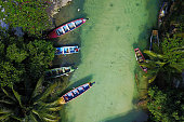 Aerial shot of White River, Ocho Rios, Jamaica with 4 colorful fishing boat moored in a small fishing settlement. Fishes are visible through the clear waters.