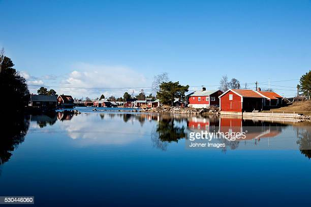 Fishing huts reflecting in water