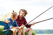 Young man and his son with fishing rod sitting by lake and having talk on summer weekend