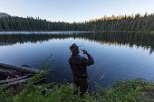 Fishing man with fishing rod at lakeside