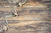 Fishing net background texture over rustic brown wood with copy space