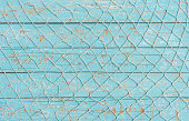 Maritime background, fishing net over light blue wooden boards.