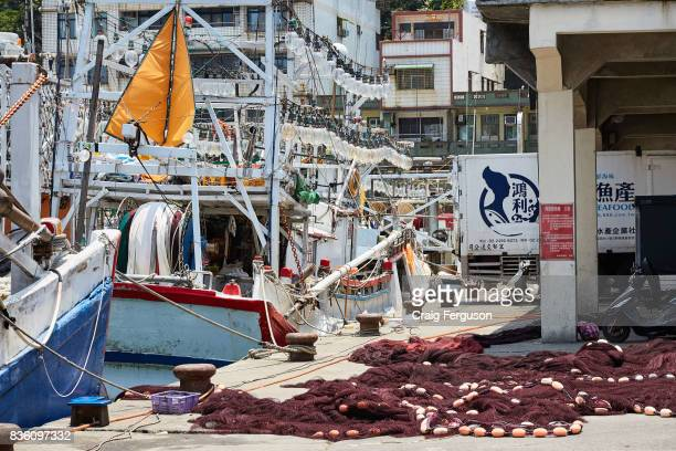 Fishing nets lie on the ground next to docked squid fishing boats Squid fishing represents approximately 10% of Taiwan's $2 billion fishing industry...