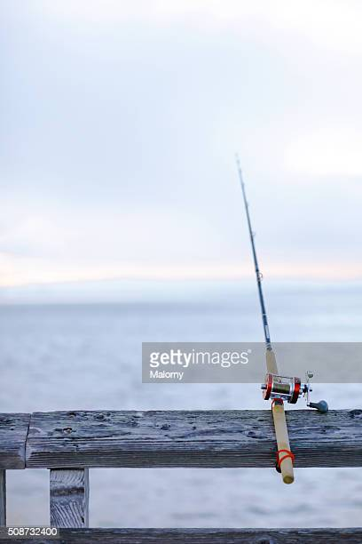A fishing pole is attached to a railing in the late afternoon.
