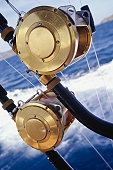 Fishing rods mounted on stern of boat, close-up of fishing reels, close-up