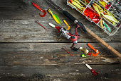 Fishing tackles - fishing spinning and box with color fishing tackles on wooden boards. Top view. Copy space