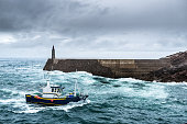Fishing vessel under storm arriving at pier. It is a boat or ship used to catch fish in the sea. There are many different kinds of vessels in commercial, recreational or fishing artisanal. Fishing can