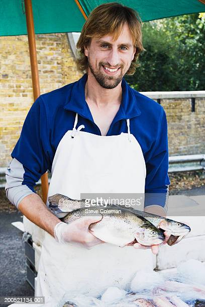 Fishmonger holding brown trout at market stall, smiling, portrait