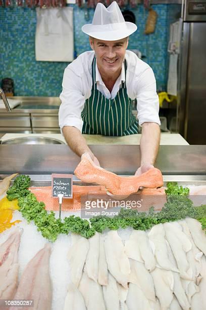 Le Fishmonger'tenant un filet de saumon