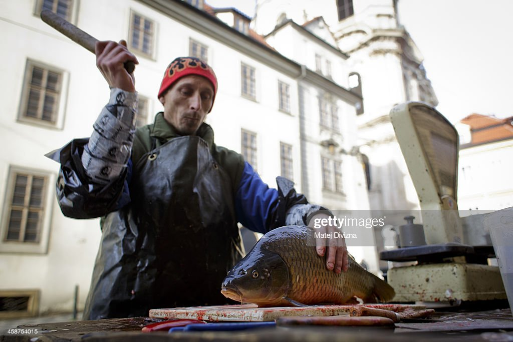A fishmonger kills a carp for a customer at his stall on December 21, 2013 in Prague, Czech Republic. In the days before Christmas, fisherman from Southern Bohemia sell their live fish on street corners for use in the traditional Czech Christmas dishes of fried carp, potato salad and fish soup.