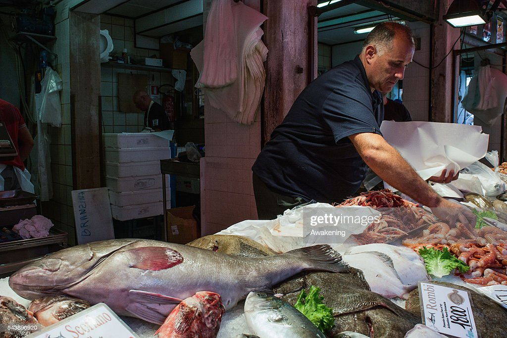 A fishmonger of the Venice Rialto Market prepares the fish on the counter on June 30, 2016 in Venice, Italy.