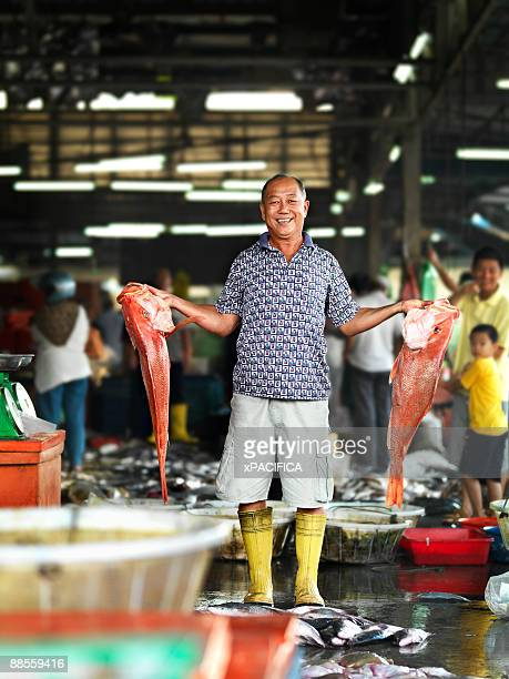A fishmonger showing off his prize fish.
