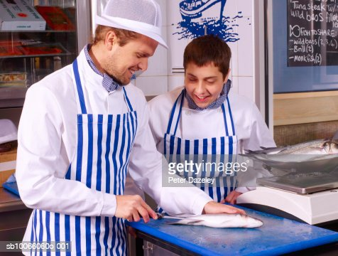 Fishmonger teaching trainee how to fillet Sea bass fish : Stock Photo